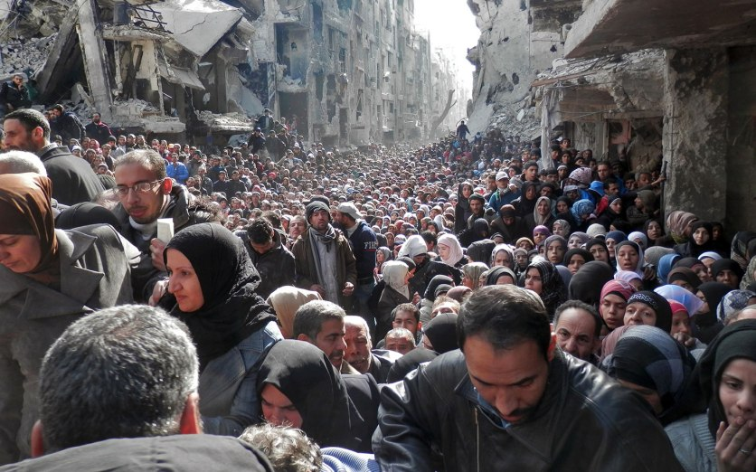 DAMASCUS, SYRIA - JANUARY 31: In this handout provided by the United Nation Relief and Works Agency (UNRWA), Residents wait in line to receive food aid distributed in the Yarmouk refugee camp on January 31, 2014 in Damascus, Syria. The United Nations renewed calls for the Syria regime and rebels to allow food and medical aid into the Palestinian camp of Yarmouk. An estimated 18,000 people are besieged inside the camp as the conflict in Syria continues. (Photo by United Nation Relief and Works Agency via Getty Images)
