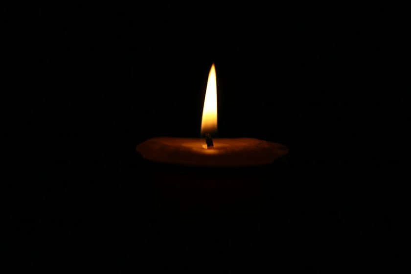 A completely dark black frame with one bright flame from a candle visible in the darkness
