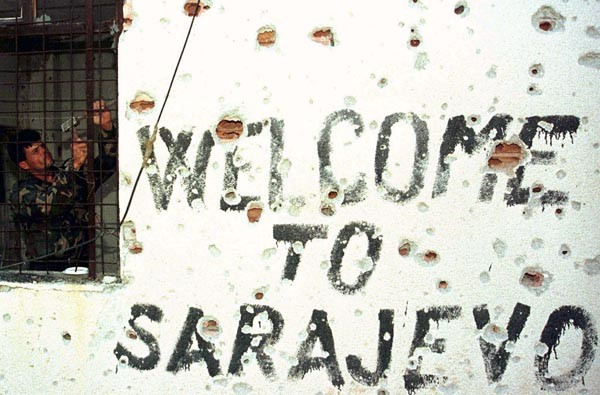 A hand painted sign reading welcome to Sarajevo covered in shrapnel caused pock-marks
